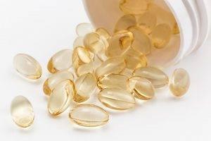 golden pills spilling out of a bottle